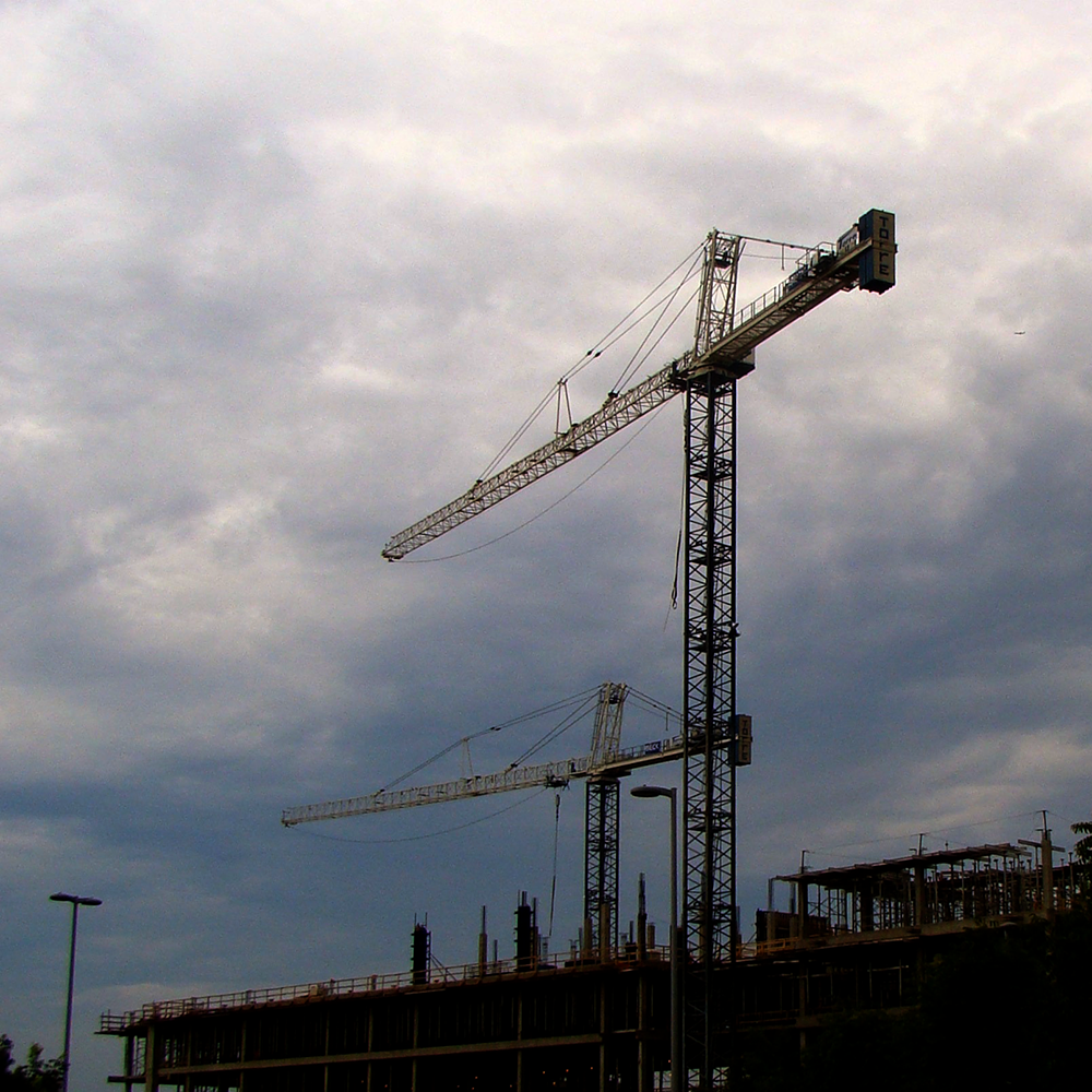 Cranes rising above a contruction site.